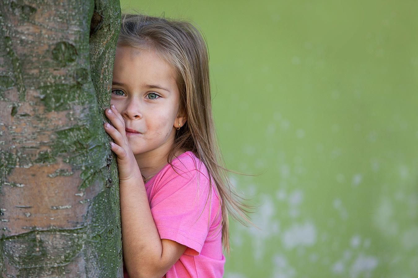 Fotografie eines Mädchens im rosa T-Shirt, hald hinter einem Baum versteckt und hervorlugend