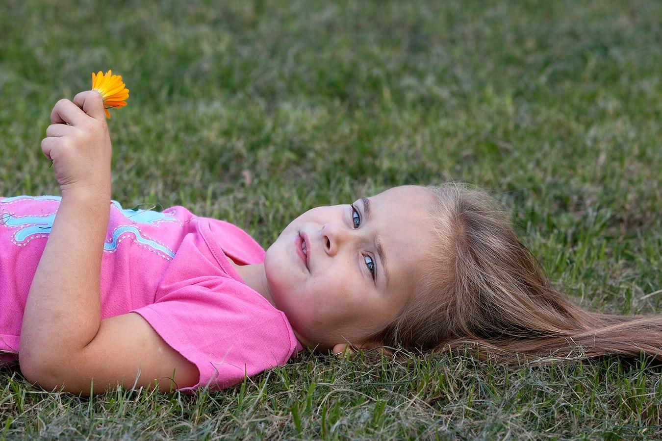 Portrait eines Mädchens liegend auf dem Rasen